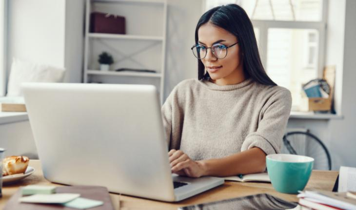 woman wearing glasses sitting behind a laptop