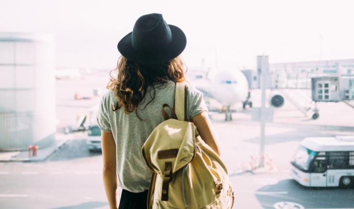 woman in a hat and wearing a backpack at the airport looking out at an airplane