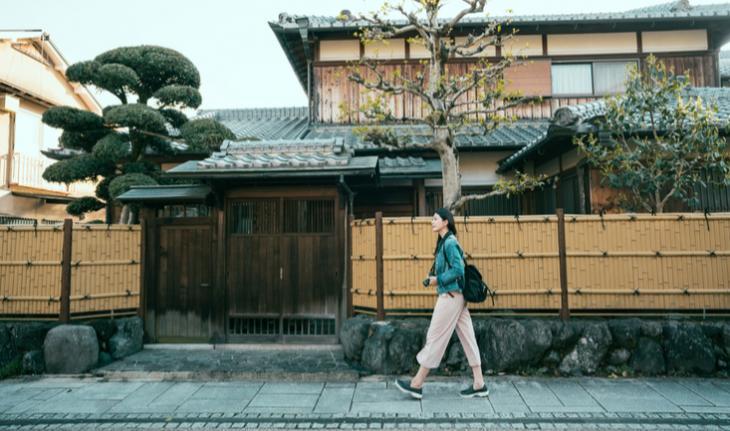 woman walking down a residential street in japan