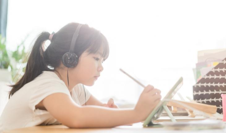 young student learning on a tablet for china new tutoring policy article
