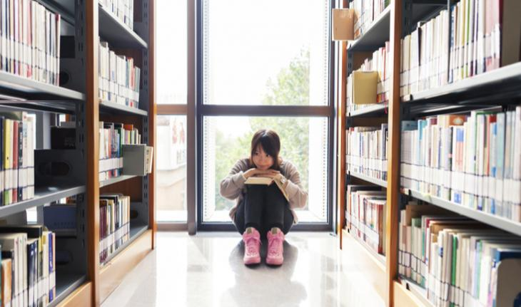 student sitting in a library for new article on china's private tutoring regulations