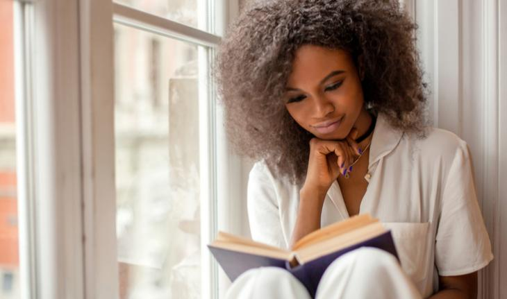 woman sitting by a window happily reading a book