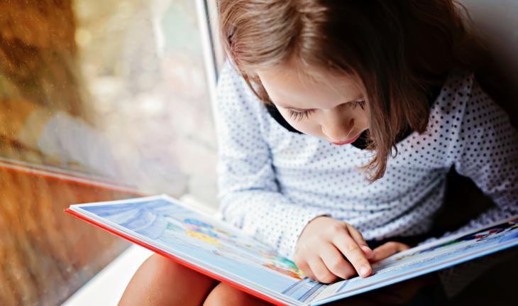 young girl reading a book by the window