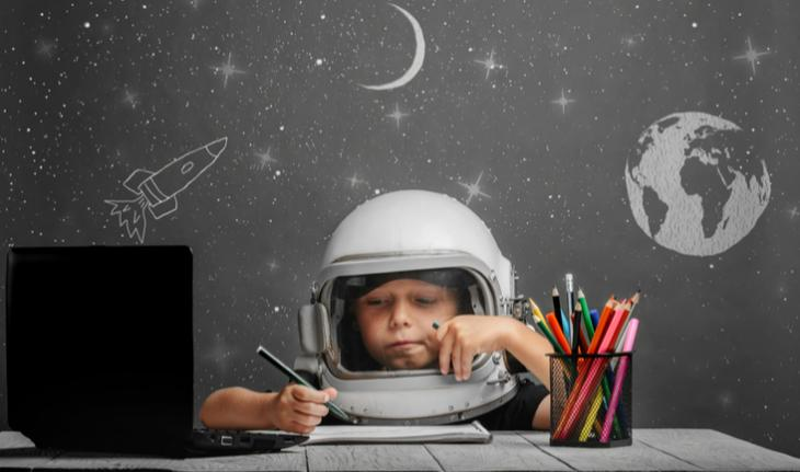 boy in a space helmet playing esl games and activities on a laptop