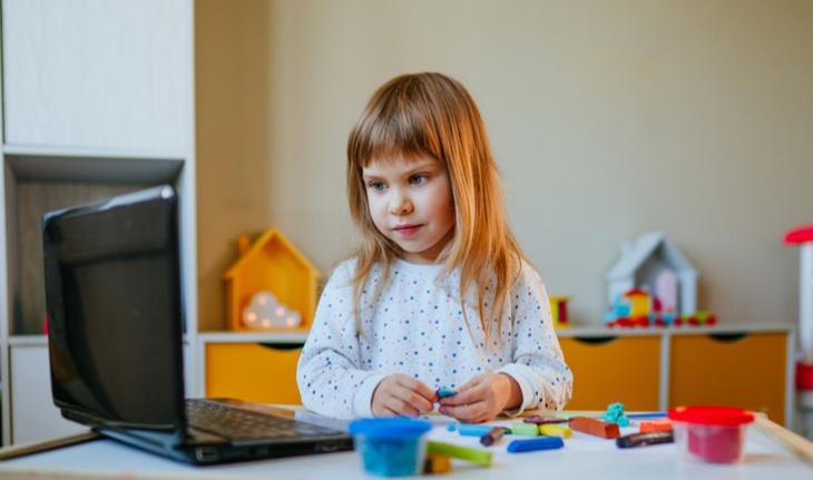 girl building blocks in front of laptop