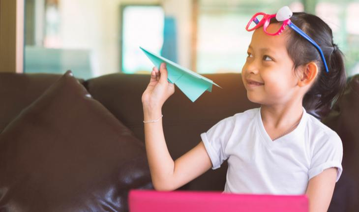 smiling girl holding a paper airplane