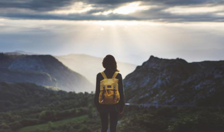 woman wearing a backpack looking out at a mountain view for article on what to know as an esl teacher going abroad