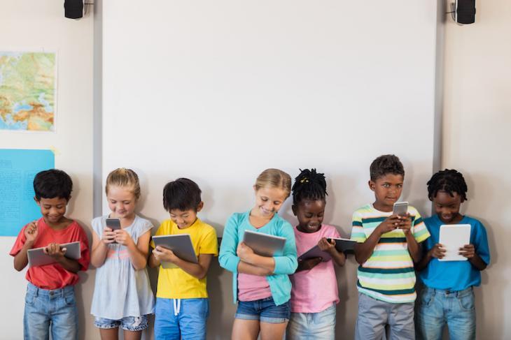 Children using technology in an ESL classroom.