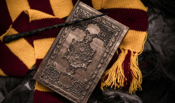 flat lay of red and yellow scarf, wand and wizard book