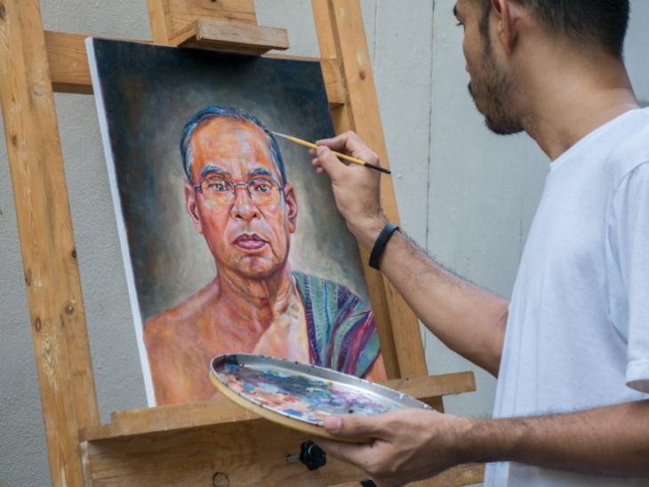 A man painting art a job that teachers can do from home.