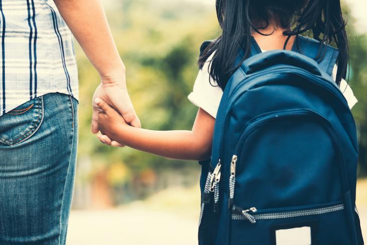 teacher holding childs hand