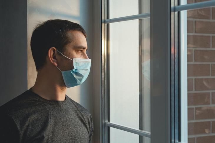 man staring out the window with mask on.