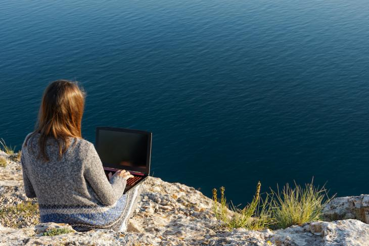 woman sitting a mountain with laptop.