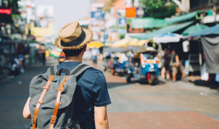traveling man walking down khao san road outdoor market in bangkok, thailand