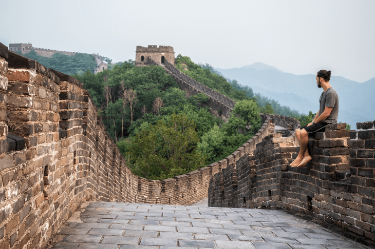 person sitting at the great wall of china - how to travel the world and make money