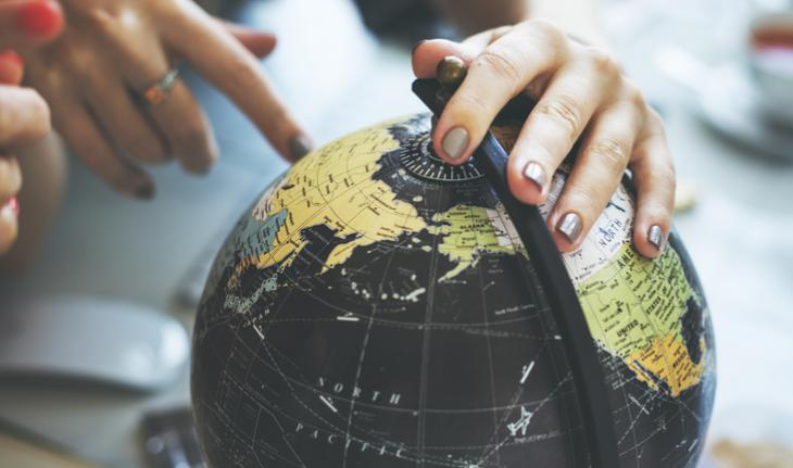 hand on a globe pointing to an unseeable destination