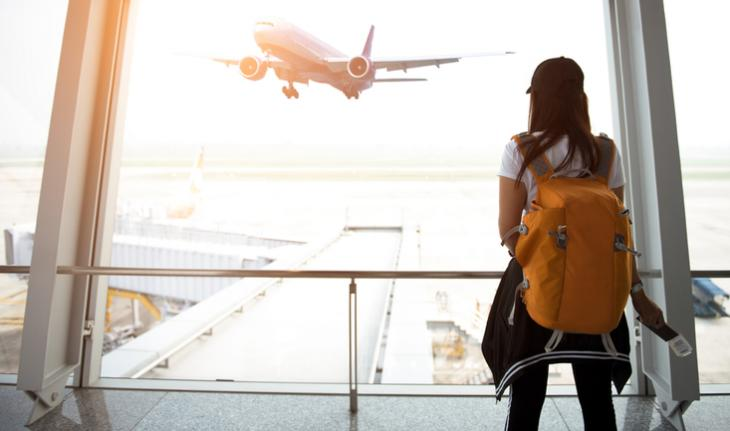 woman in a backpack at the airport watching an airplane