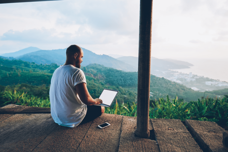 man on laptop studying TEFL certification online while traveling