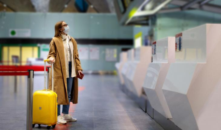 woman wearing a mask at an airport kiosk