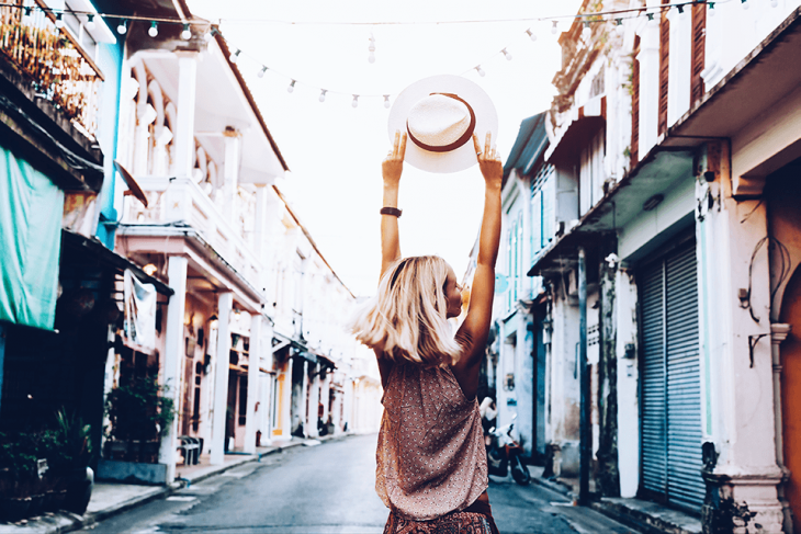 excited woman traveling walking down street holding hat