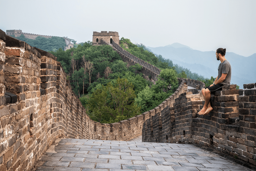 young traveller sitting on Great Wall of China