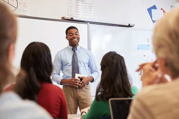 male teacher leading business English lesson in classroom