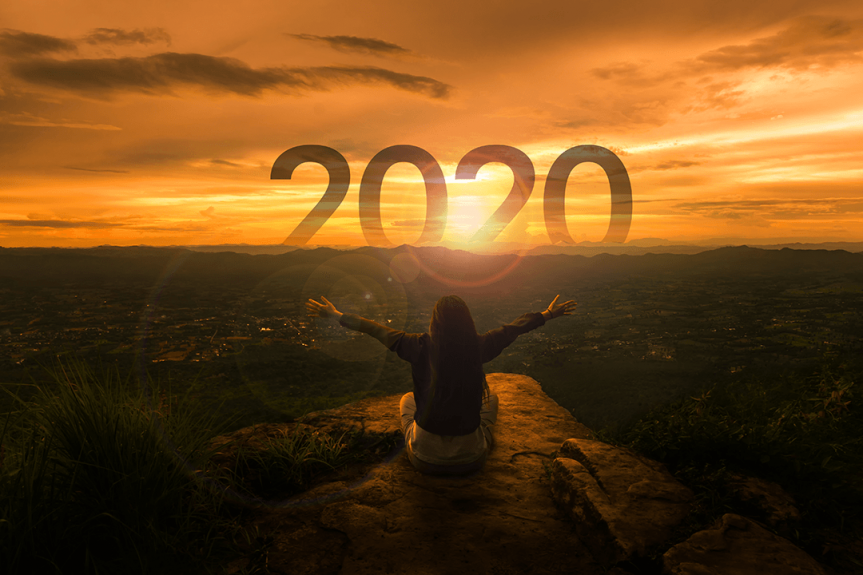 Traveler looking at a sunrise with optimism for 2020
