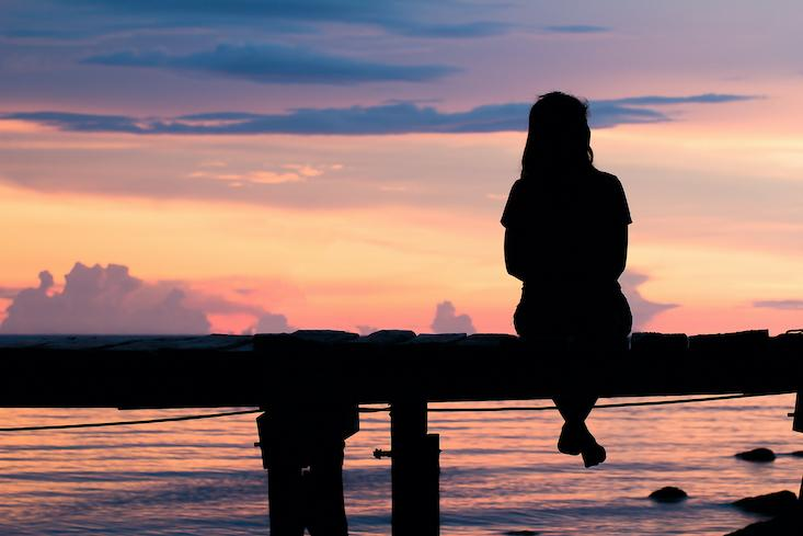 woman sitting at sunset dreaming of travel - how to teach in a different country