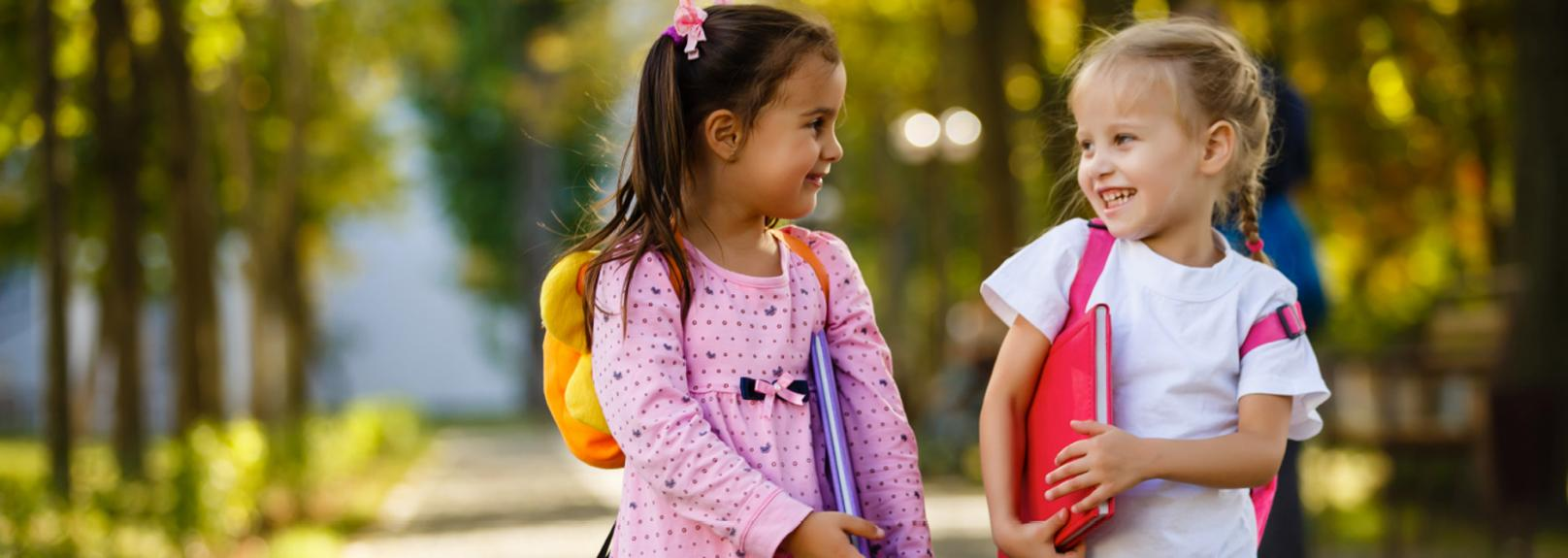 Two young girls wearing backpacks and carrying school books - early childhood education recruitment agency