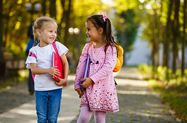 Two young girls wearing backpacks and carrying school books - Teacher recruitment